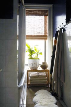 A light-filled, narrow bathroom is accented with a sheepskin rug and bamboo roller blinds.