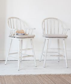 Loaf's scuffed white kitchen stools with comfy natural linen seat cushions and hooped backs. Perfect for farmhouse kitchens and country homes