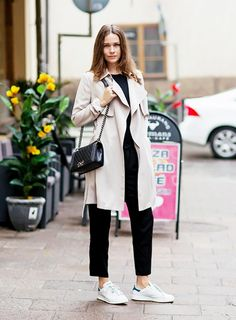 Give your standard cropped trousers a fresh look by wearing them with a flowy trench coat and sporty sneakers.
