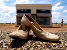In the Texas desert near the little town of Marfa, on a stretch of Highway known as the loneliest road in America, sits the Prada store. It's fully stocked with bags and shoes and although the automatic doors don`t open the lights do come on at night, making its glowing glass frontage the only illumination for miles around. It's a permanent art installation, built by a Berlin-based artistic couple with the approval of Prada herself- who provided their logo and the goods on display.