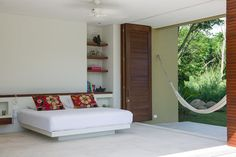 Puertas de madera conectan la alcoba principal con una terraza que da al jardín, donde una hamaca reitera el objetivo de la vivienda: el descanso. La cama es de mampostería, junto con la biblioteca, para componer un espacio limpio y sobrio.