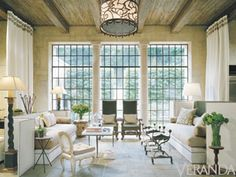 Restoration glass in steel frames and a vaulted ceiling combine with  antiques and sumptuous seating - design by Bobby McAlpine and Ray Booth .