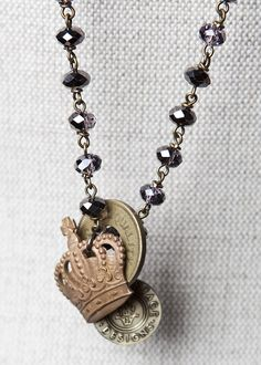 Brass crown, antique amusement park token & original @saintvintage tag are all charms on this midnight bead necklace! Click + take a closer look.