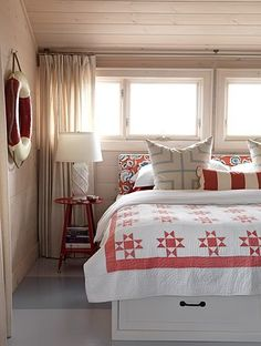 Under the bed storage, low fabric headboard as our window is low and directly above the bed. Love the red and aqua
