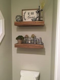 """Farmhouse bathroom decor: What to put on the wall above the toilet? I say floating shelves and some neutral farmhouse decor! The """"Be Our Guest"""" sign is perfect for this guest half bath. All of this is from Hobby Lobby and costs less than $100!"""