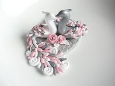 A lovely twinkling peacock wedding cake topper handsculpted from polymer clay in pink, white and grey colours. The sculpture is of two peacocks