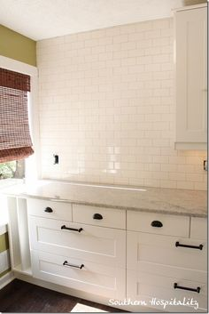 DIY: Subway tile how to. Classic kitchen look with subway tile, Carrera marble counters & shaker cabinetry.
