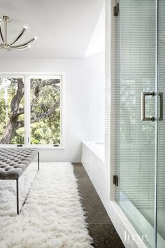 A carpet from Flokati Rugs in Jersey City, New Jersey, is juxtaposed with sleek surfaces, such as limestone flooring from Stone Source and walls clad with tiles from Ann Sacks, in the spa-like master bathroom. A fixture from Arteriors illuminates the scene, which includes a Kohler bathtub purchased from Moore Supply Company.