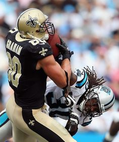 Charles Godfrey #30 of the Carolina Panthers hits Jimmy Graham after a catch