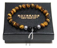 Wear this bracelet as your good luck talisman wherever you may go. Tiger's Eye is a member of the quartz family and is a protective stone carried as a talisman against ill wishes. It grounds and facilitates manifestation of the will and balances yin and yang energies. Made in our New York studio with 8MM shiny black onyx, tigers eye,  silver hematite and .925 sterling silver lucky wishbone (not plated).