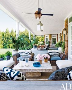 On the rear porch, wicker seating surrounds a teak table by Andrianna Shamaris | archdigest.com