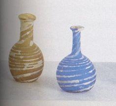 1000 v Chr. waren er al heel kunstige glazen parfumflesjes in gebruik. De meest waren donkerblauw. opaak of doorschijnend en versierd met blauwe, witte of gele ...
