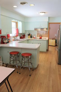 Cute mid-century kitchen renovation.  * magnetic towel rod on fridge * bread box on counter next to toaster * knives in corner
