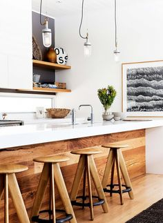 I love this kitchen!  The wood floors and bar, the stools, the Japanese style black and white art.  Love it!
