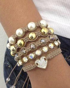 Kit de pulseiras shambalas, confeccionadas em macramé, com cordão encerado na cor kaki caribe, composto de 5 pulseiras, sendo:  - 1 pulseira de coração com strass  - 1 pulseira de corrente de strass  - 1 pulseira de cristais facetados  - 1 pulseira de pérolas douradas  - 1 pulseira de pérolas    ...