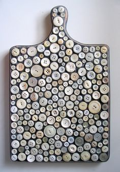 collaging a couple hundred white vintage button onto a wooden cutting board. The board has been beautifully distressed for an antique feel and the piece is coated on both sides with a protective gloss varnish.