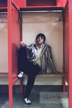 John Lennon, pictured in his trademark glasses and a stripy jacket relaxes backstage at the Shea Stadium, New York, on August 24, 1966