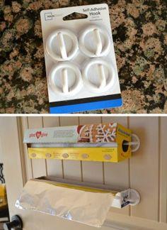 Easy Inexpensive Kitchen Organizing Tips - use plastic self adhesive hooks as plastic wrap holders idea via Ask Anna