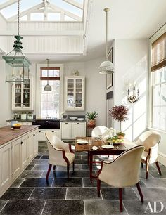 An antique Federal table furnishes the breakfast area of a historic home in Hudson Valley, New York. The spacious kitchen was converted from a former conservatory space.