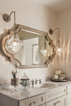 luxurious bathroom with beautiful gold mirror and light fixtures