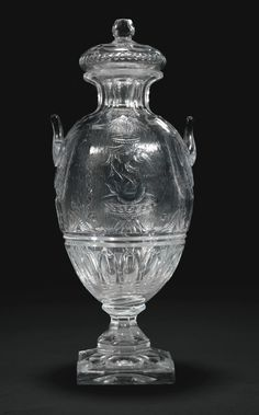 A `rock crystal' glass two-handled vase and a cover, probably Thomas Webb or Stevens and Williams, Stourbridge, late 19th century the oviform body wheel cut on one side with a dolphin fountain, the reverse with trellis frame, the shoulders set with short upright shell cut handles, raised on a short facet-cut stem and square base, the shallow domed cover with facet-cut ball finial,