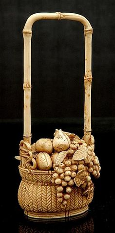 A Japanese carved ivory basket of fruit Meiji period 1868 - 1912 Realistically modelled depicting berries and vine with stone fruit contained within a woven basket and elongated bamboo handle 16.5 cm.