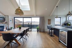 Open plan kitchen, dining and living with skylight providing extra natural light. Open Plan Kitchen, Kitchen Dining, Drinks Cabinet, Ceiling Beams, Skylight, Natural Light, Man Cave, Living Spaces, New Homes