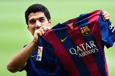 Luis Suarez of FC Barcelona holds a FC Barcelona shirt during his presentation as new FC Barcelona player at Camp Nou on August 19, 2014 in Barcelona, Catalonia.