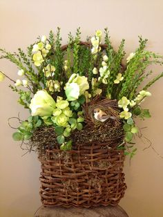 Custom floral arrangement door hanger wooden basket with cherry blossoms, tulips, greenery, flowers, periwinkle, twine and nest with bird.