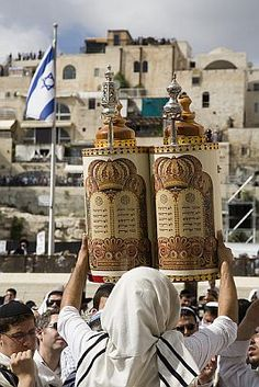 A Jewish man lifts the Sefer Torah in Jerusalem so all can see the Holy Scripture written on the scroll, which is protected inside the case.