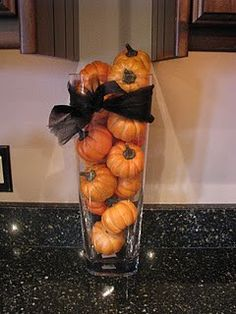 cute vase of baby pumpkins tied with black ribbon.