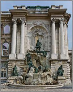 MÁTYÁS-KÚT, BUDAPEST - A Várpalota Hunyadi udvarát díszíti a királlyá lett Hunyadi Mátyás kútja, Stróbl Alajos szobrász 1904-ben felállított munkája (az építész Hauszmann Alajos volt). - A Stróbl Alajos által készített kút egy sziklatömböt ábrázol, melyből forrás tör elő. A forrás felett Mátyás király áll vadászöltözetben, lábainál elejtett szarvas, körülötte kíséretének tagjai vadászkutyáikkal, melyek szomjukat oltanák a forrás vizéből.