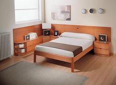La cabecera de la cama esta unida a las mesas de noche y a una comoda