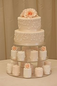 I like theses mini cakes with the same blush pink ribbon lining the bottom as the main cake & a mix between a pearl topping & flower topping