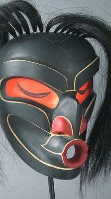 Ira Etzerza, the carver, is from the Wolf Clan of the Tahltan tribe, Kwakiutl people (more properly called Kwakwaka'wakw).  In the mythology of the Kwakwaka'wakw people, the Dzunukwa, or Cannibal Woman, is a dangerous monster. Twice the normal height, with a black, hairy body and sagging breasts, she lurks in the forest and eats children. The Cannibal Woman is represented by a mask such as the one shown here, worn by a dancer during a Winter Ceremony.