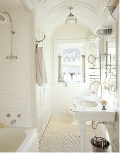 beautiful white bathroom with subway tile, exposed shower pipe, vintage style sink.