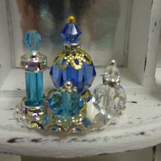 Handmade perfume bottles for dolls houses. Approx height largest smallest Glass beads and 2 Swarovski crystals. Miniature Bottles, Miniature Crafts, Miniature Fairy Gardens, Barbie Accessories, Dollhouse Accessories, Diy Dollhouse, Dollhouse Miniatures, Bead Bottle, Barbie Makeup