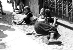 Warsaw ghetto, Poland, 1941. A man lying in the street, next to two children.