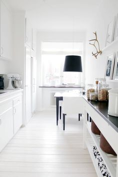 An all white kitchen with a touch of black feels clean and modern.