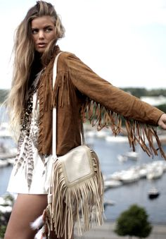 fringed jacket on a wavy haired model. The fringed purse is a nice touch. The dress could probably stand to be a few inches longer though.