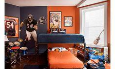 Este es el segundo dormitorio, las paredes son de color negro y naranja, sobre la cama hay un balon de futbol y en la pared hay el uniforme de deportes de un jugador de fútbol americano. Federico.
