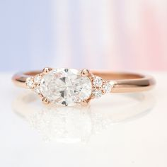 Meet the newest cluster-accented beauty to join our custom design gallery! - Meet the newest cluster-accented beauty to join our custom design gallery! It has an East-West set - Dainty Engagement Rings, Design Your Own Engagement Rings, Oval Engagement, Engagement Ring Sizes, Beautiful Engagement Rings, Oval Diamond, Simple Jewelry, Wedding Rings, Custom Design