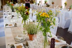 Relaxed wedding table arrangements. Jars and bottles filled with garden flowers and pots of herbs.