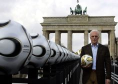 Franz Beckenbauer, president of Germany's World Cup organising committee, holds a golden soccer ball during a presentation next to the Brandenburg Gate in Berlin, 18 April 2006