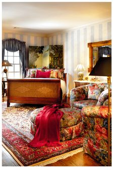 Colorful daughters bedroom room, charming screen behind the bed and a pair of lively print chairs