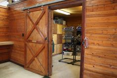 Sliding door to tack room with gorgeous natural wood.   broughtonperformancehorses.com