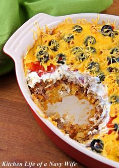 Mexican Casserole - (refried beans, tortilla chips, ground beef, salsa, sour cream, tomatoes, cheddar cheese, black olives)