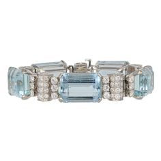 Platinum flexible vintage bracelet consisting of 5 emerald cut aquamarines having a total weight of approximately 100 carats set with approximately carats total weight of round brilliant cut diamonds, circa Gemstone Jewelry, Jewelry Bracelets, Jewelery, Blue Bracelets, Jewelry Box, Bangles, Pearl And Diamond Necklace, Aquamarine Bracelet, Diamond Bows