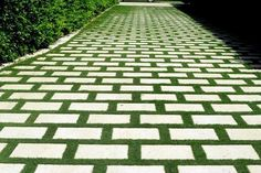 A Palm Beach home has a driveway made of pavers with grass joints: