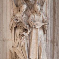 El ángel de la izquierda tañe un fidula deteriorada en la que no puede verse el clavijero. El de la derecha tiene un pequeño laúd. Las cuerdas las pulsa con los dedos.